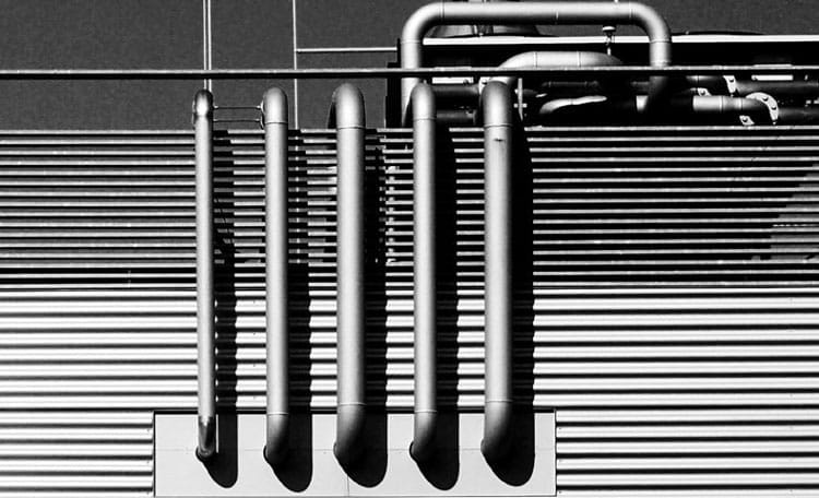 black and white industrial building exterior with exposed pipes