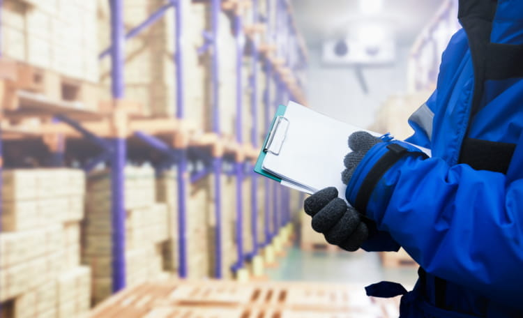 Hand of quality control worker checking goods on delivery in the cold room warehouse
