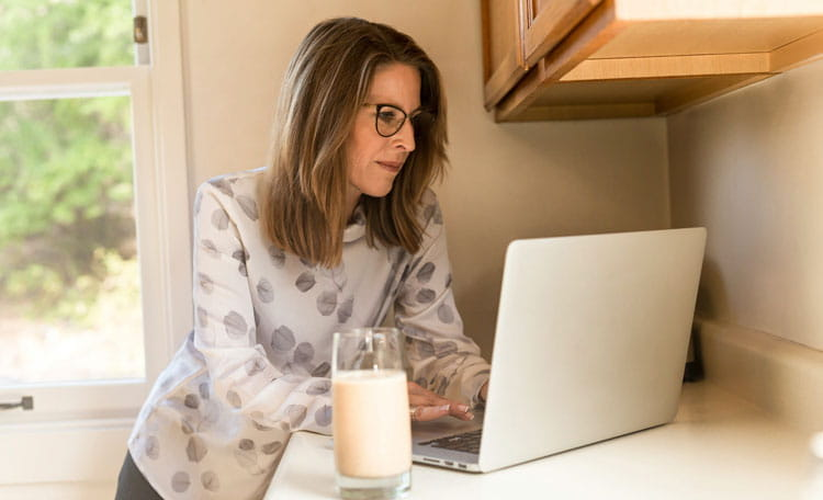 Woman working on laptop in kitchen with glass of milk