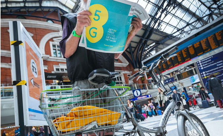 cyclist at UK train station holding newspaper with 5G ad