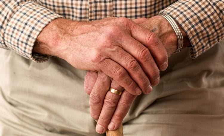 elderly gentleman's hand place over each other on walking stick