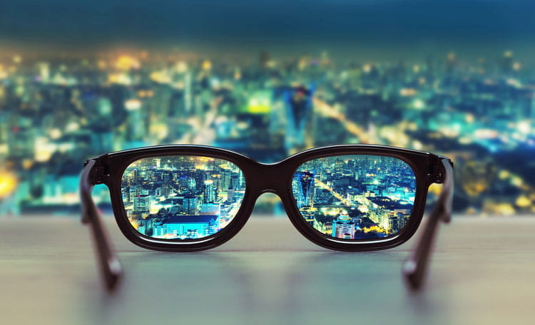 glasses on desk inside skyscraper office looking out at night time city