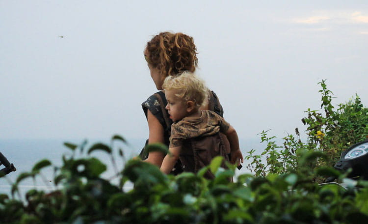 Mother walking in countryside with toddler on back